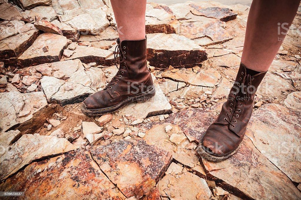 The feet of a young woman standing on some rocks royalty-free stock photo