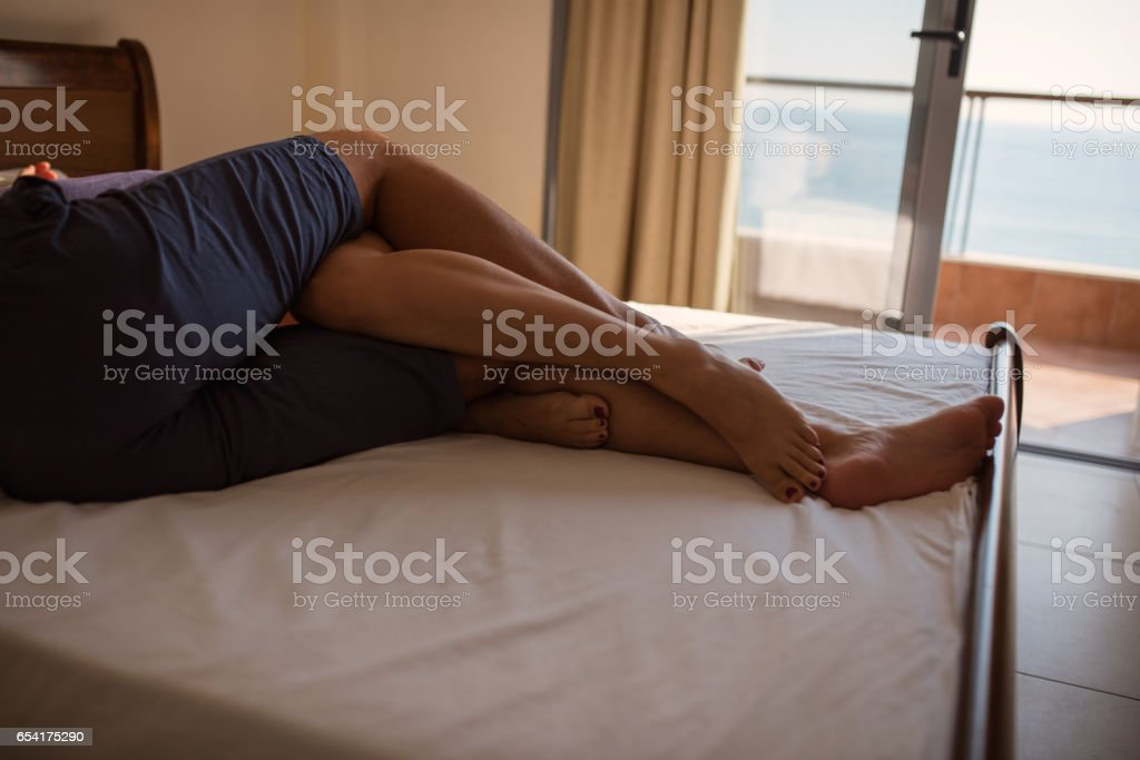 The feet of couple in bed stock photo