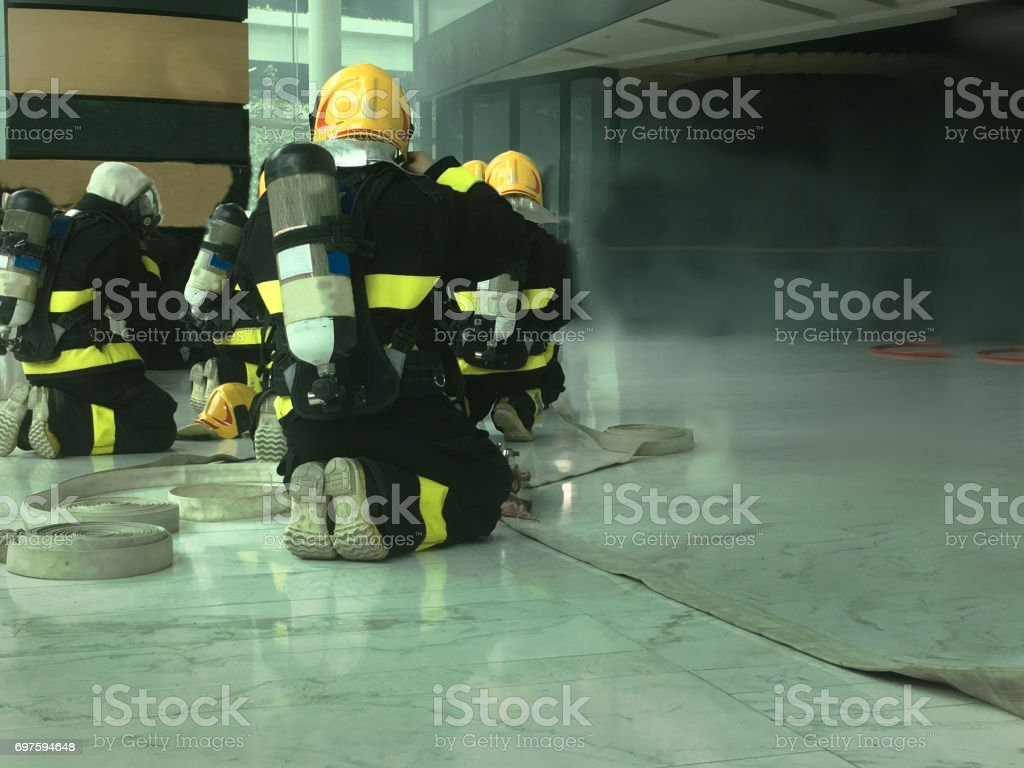The fireman mustering for extinguishing the fire inside the building stock photo