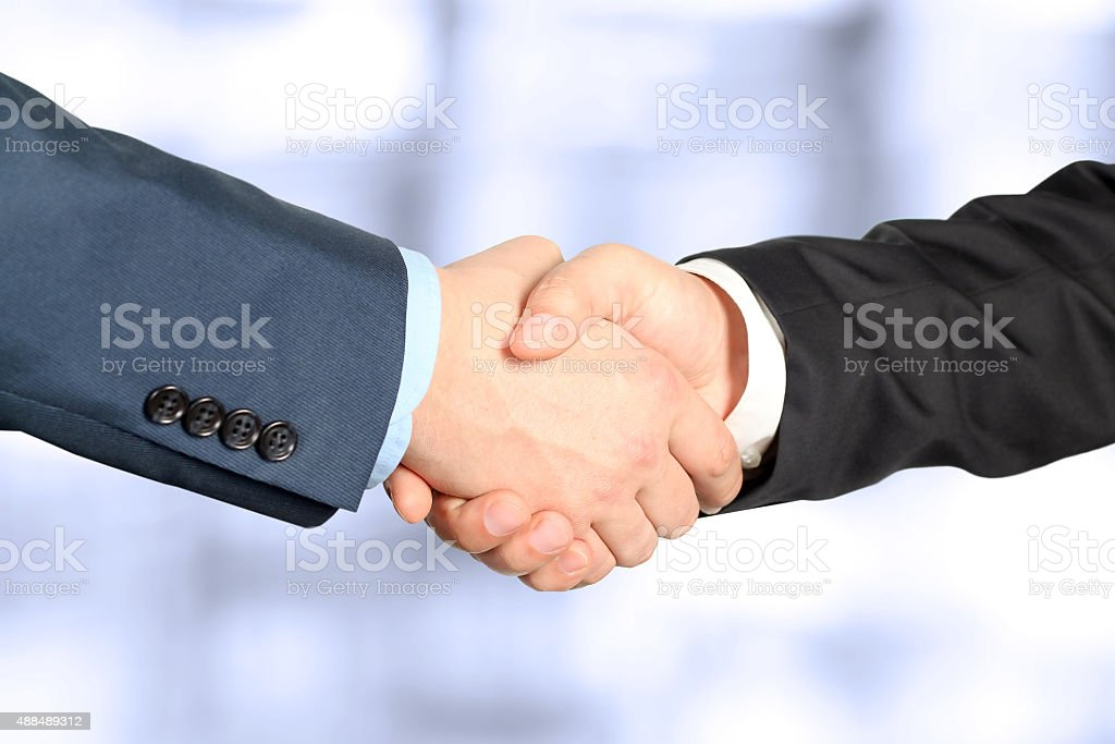 The firm handshake  between two colleagues in office. stock photo