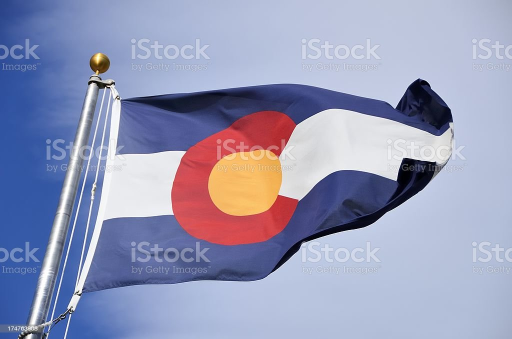 The flag of the state of Colorado against a clear blue sky stock photo