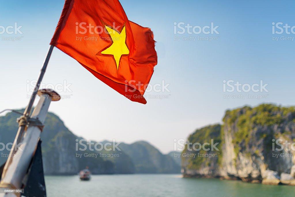 The flag of Vietnam fluttering in the Ha Long Bay stock photo