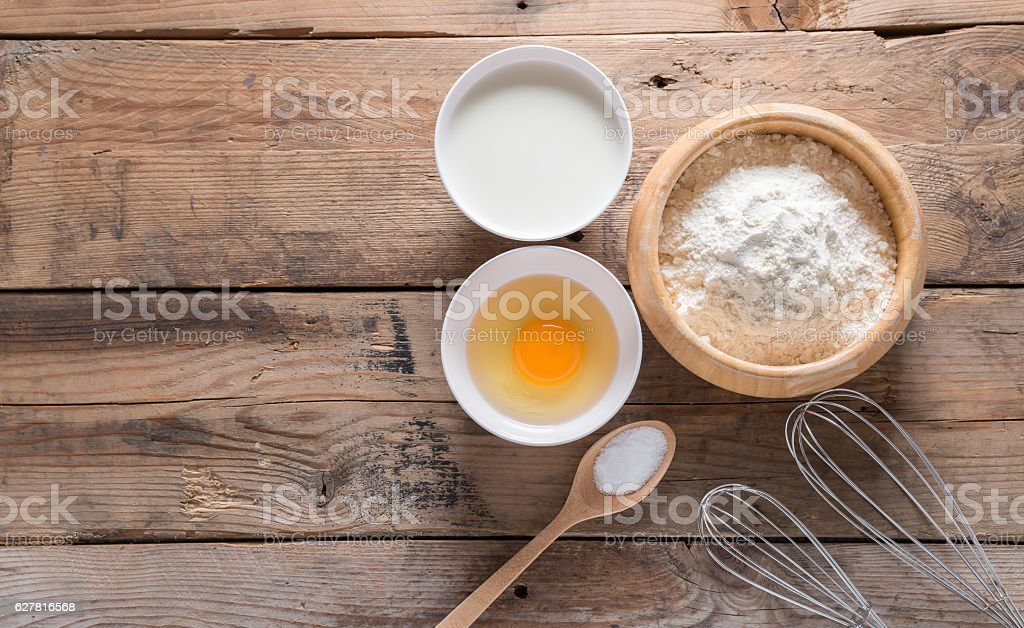 The flour in wooden bowl, egg, milk and whip. stock photo
