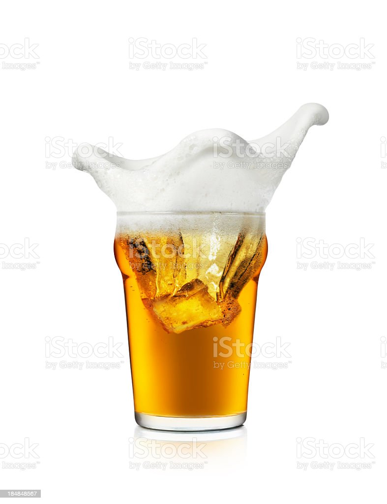 The foam on a glass of beer splashing the edges of the cup stock photo