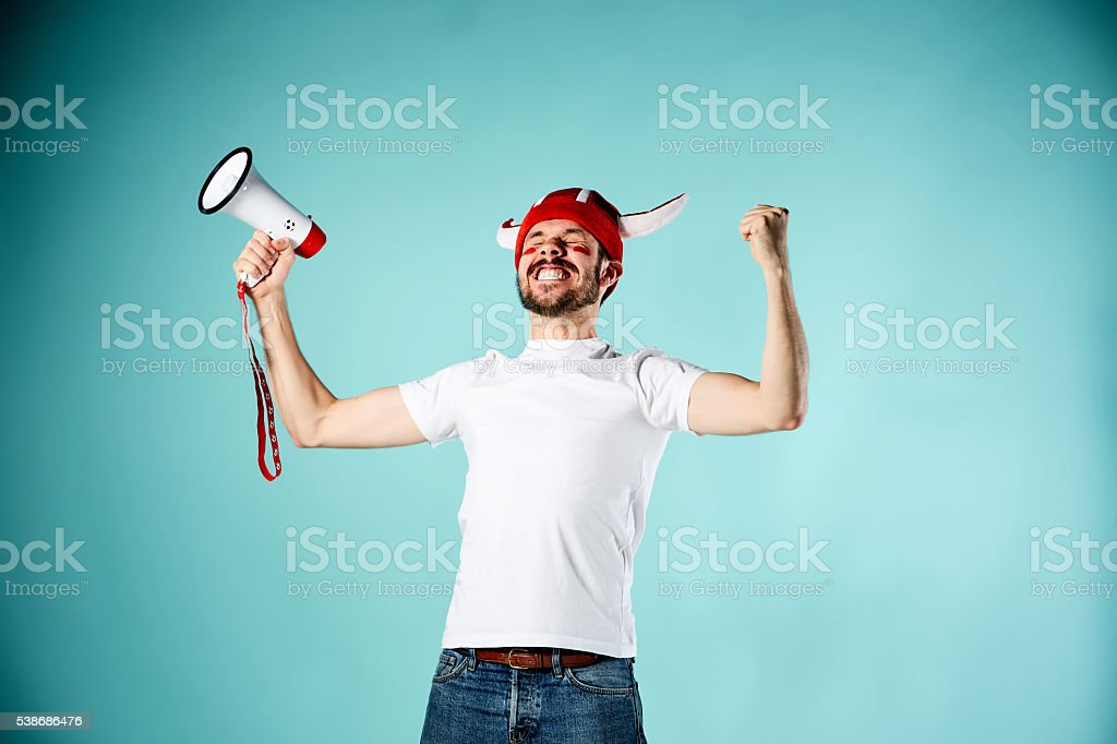 The football fan with mouthpiece over blue background