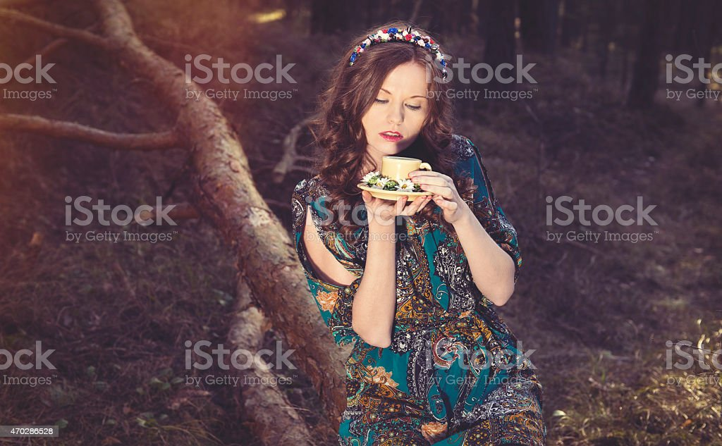 The forest nymph meditates in the fantastic wood with a mug stock photo