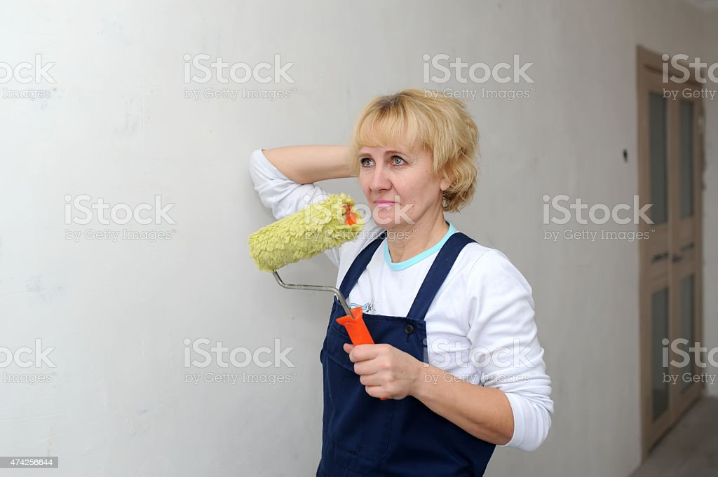 the forewoman glues wall-paper in the room stock photo