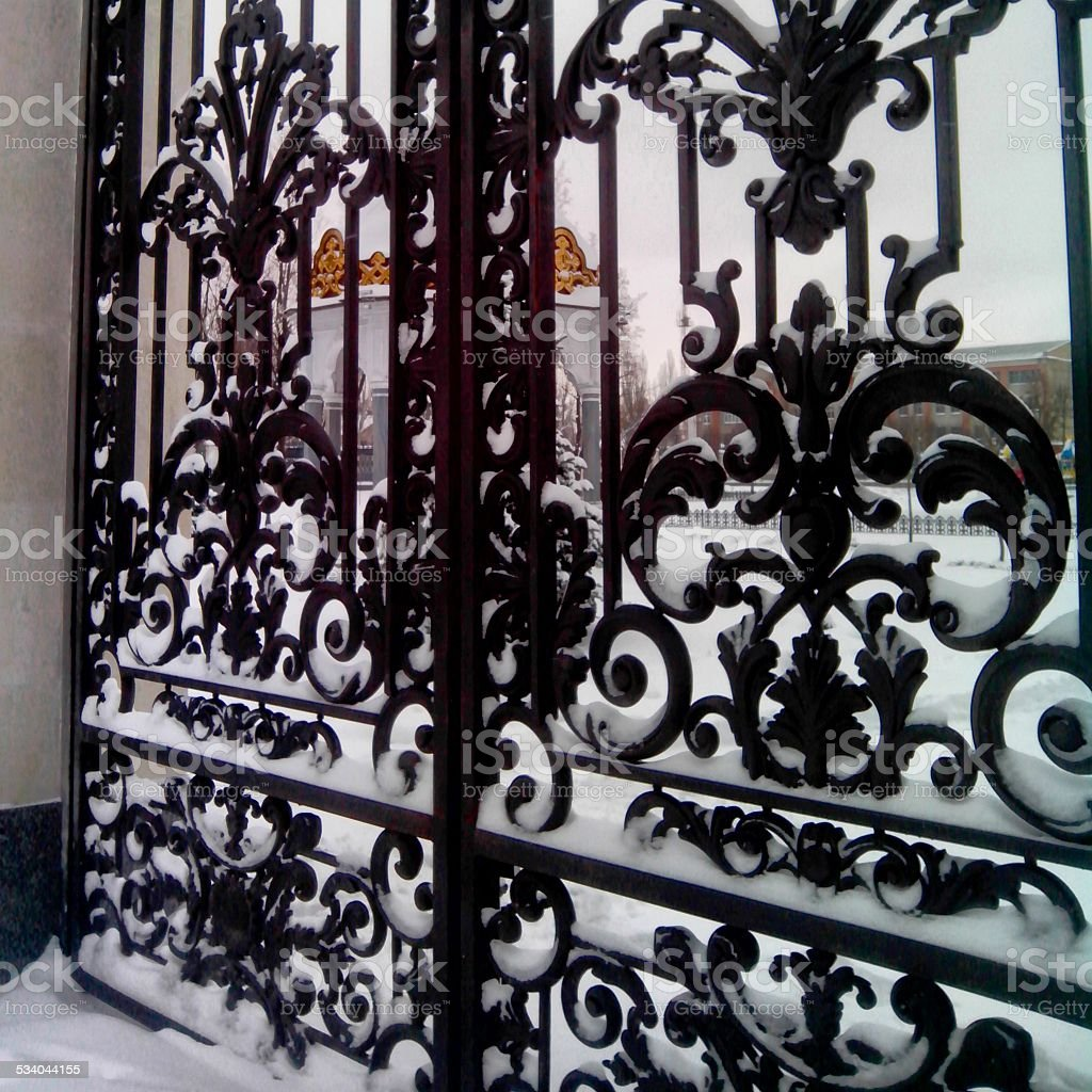 The forged iron gate in snow. stock photo
