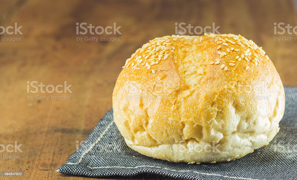 the fresh bread  on the wood background, warm toning, selective stock photo