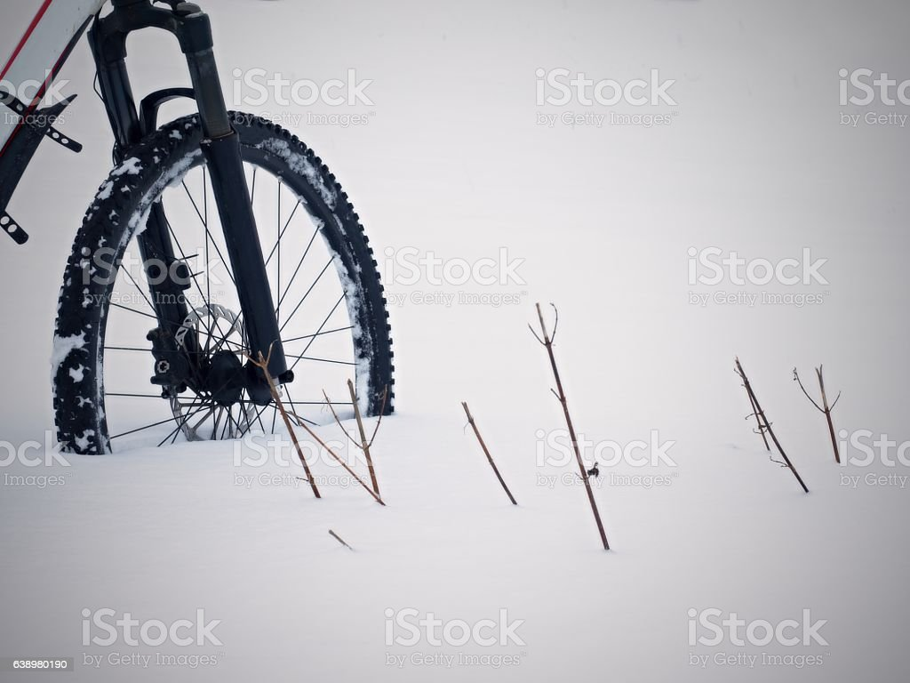 The front wheel of bike stay in snow. Lost path stock photo