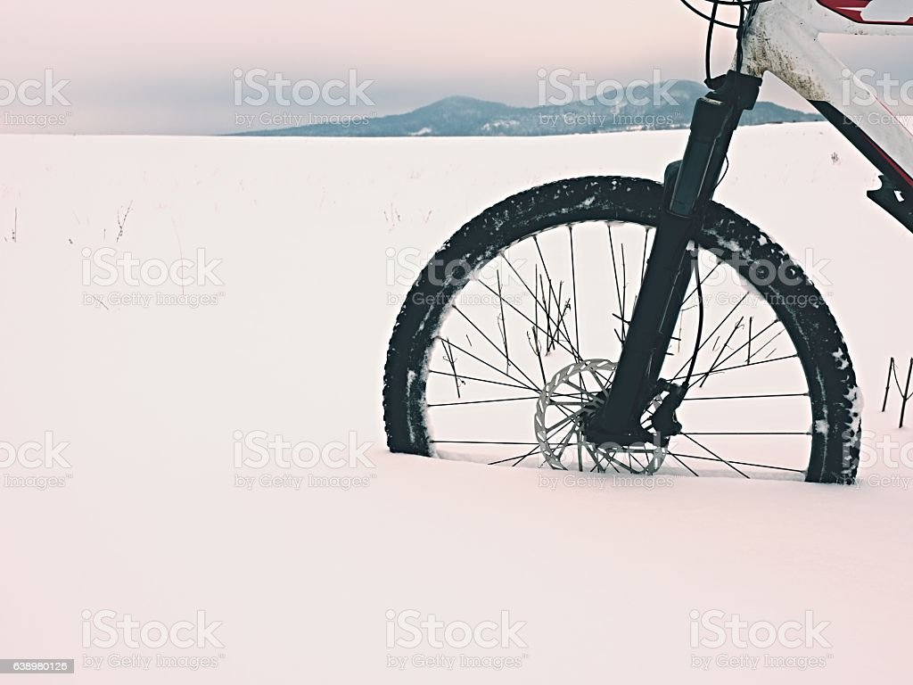The front wheel of mountain bike stay in powder snow. stock photo