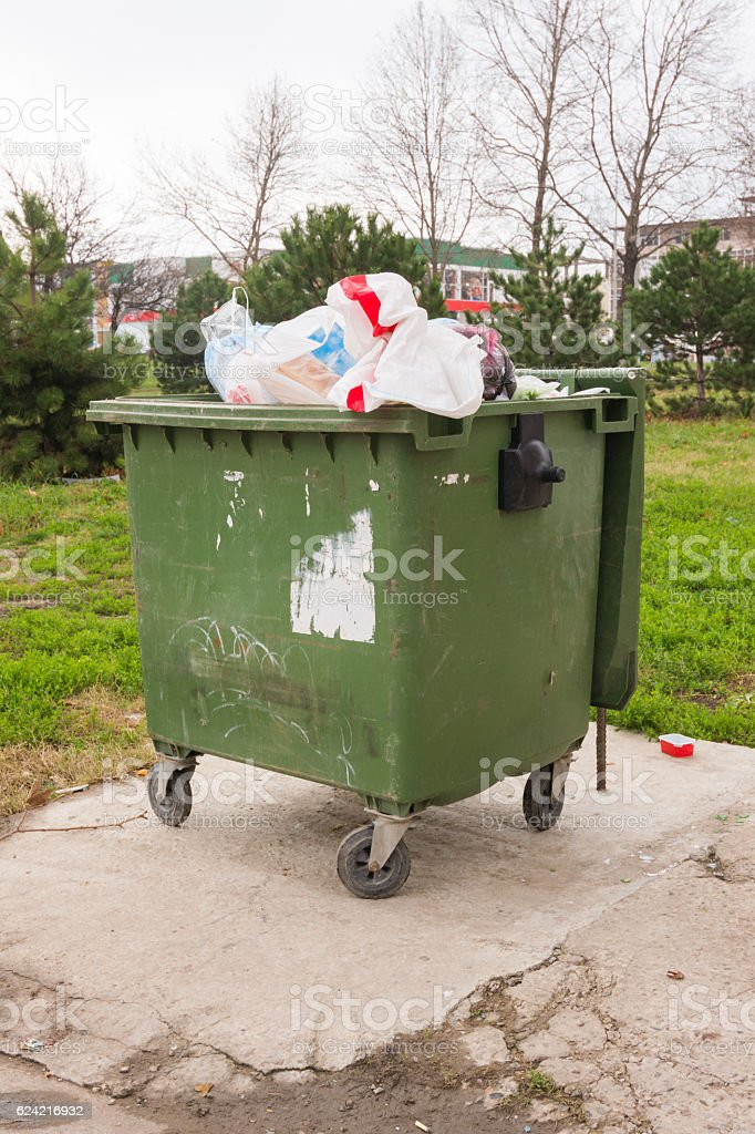 The garbage container on wheels completely packed with trash stock photo
