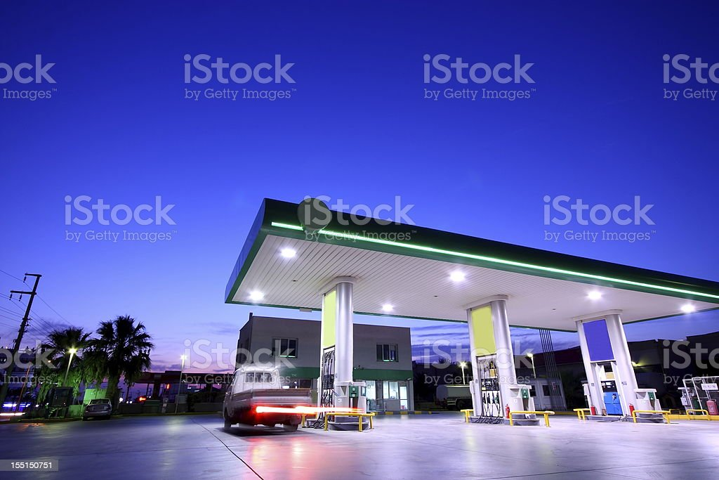 The gas station is well lit at night stock photo