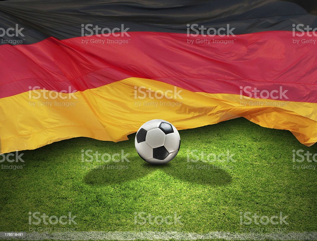 The German flag flies behind a soccer ball and grass stock photo