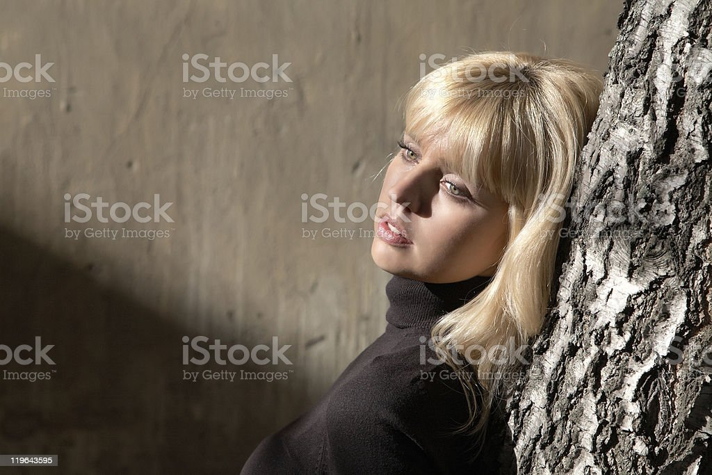 The girl at  tree against a wall stock photo