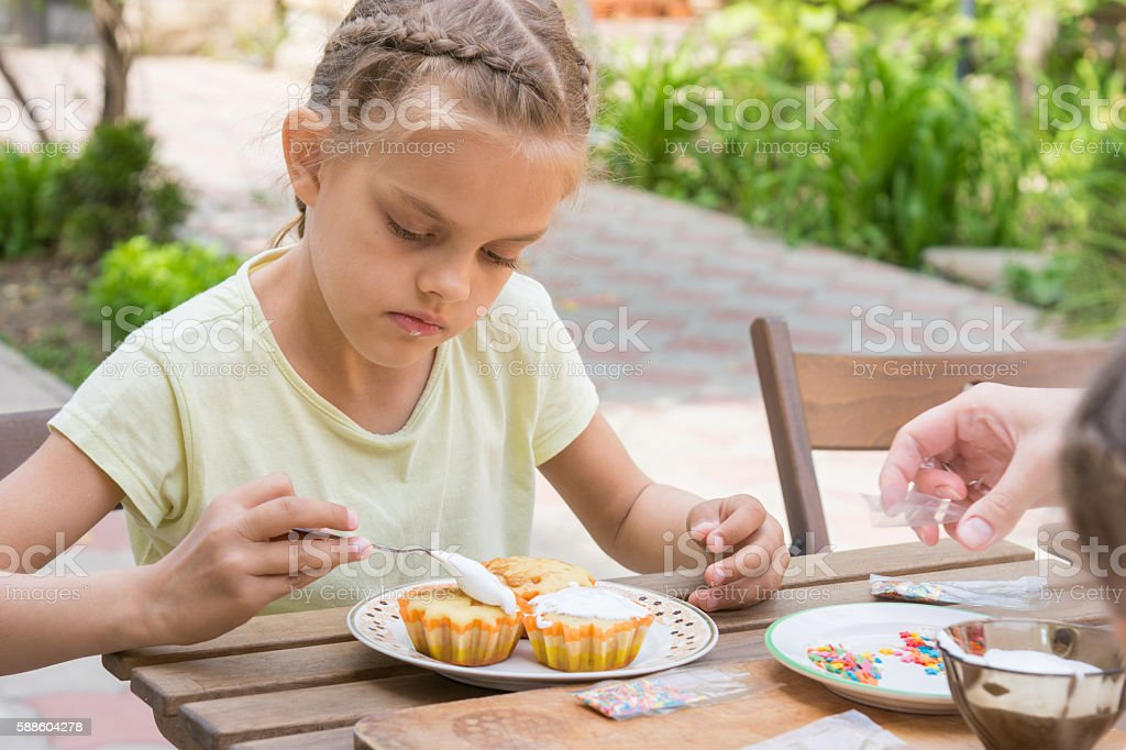 The girl carefully coated with confectionery glaze Easter cupcakes stock photo