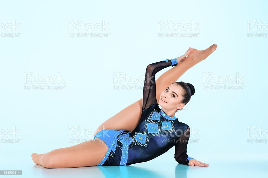 The girl doing gymnastics dance on a blue background stock photo