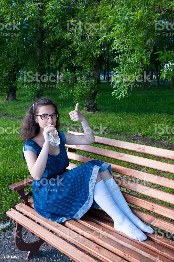 The girl drinks water and shows a hand sign 'OK' stock photo