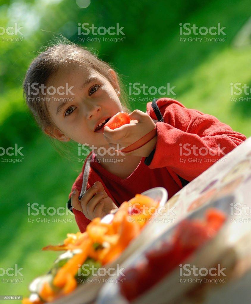 The girl eats a tomato royalty-free stock photo
