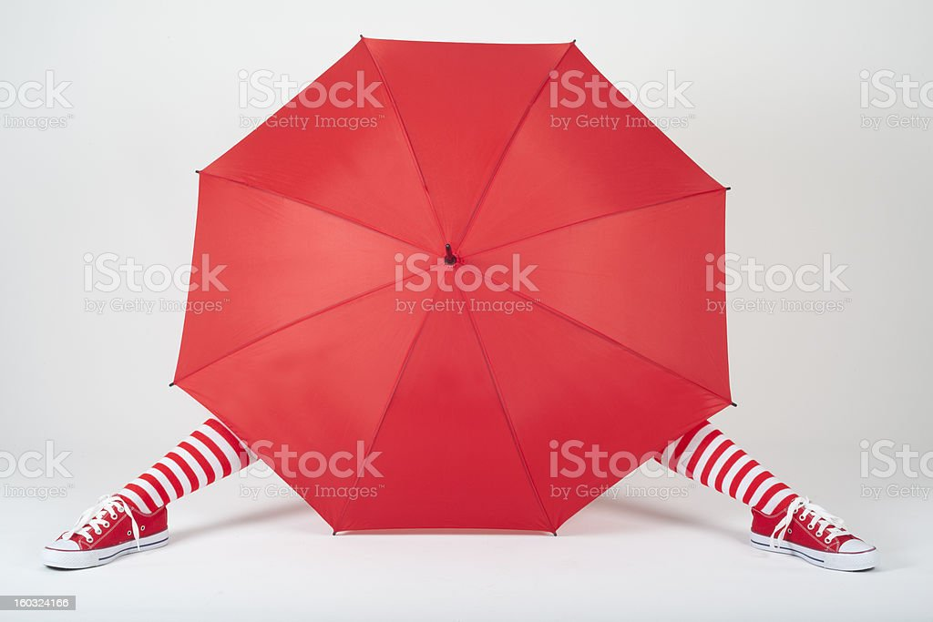 The girl hiding behind a large red umbrella royalty-free stock photo