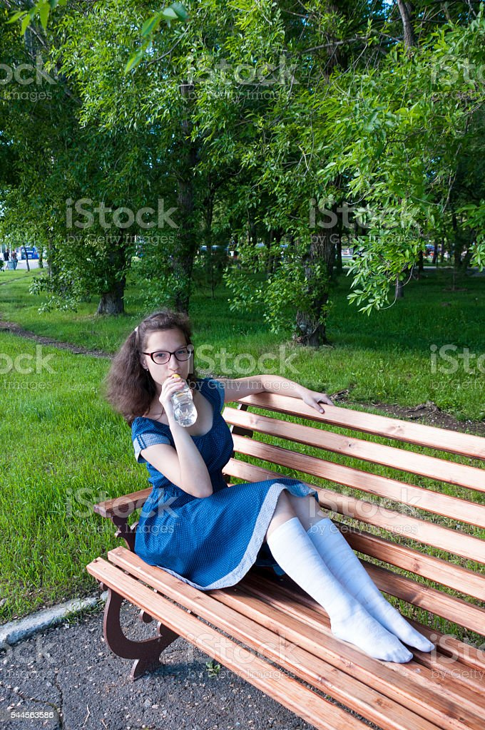 The girl in a park drinking water on a wooden bench stock photo