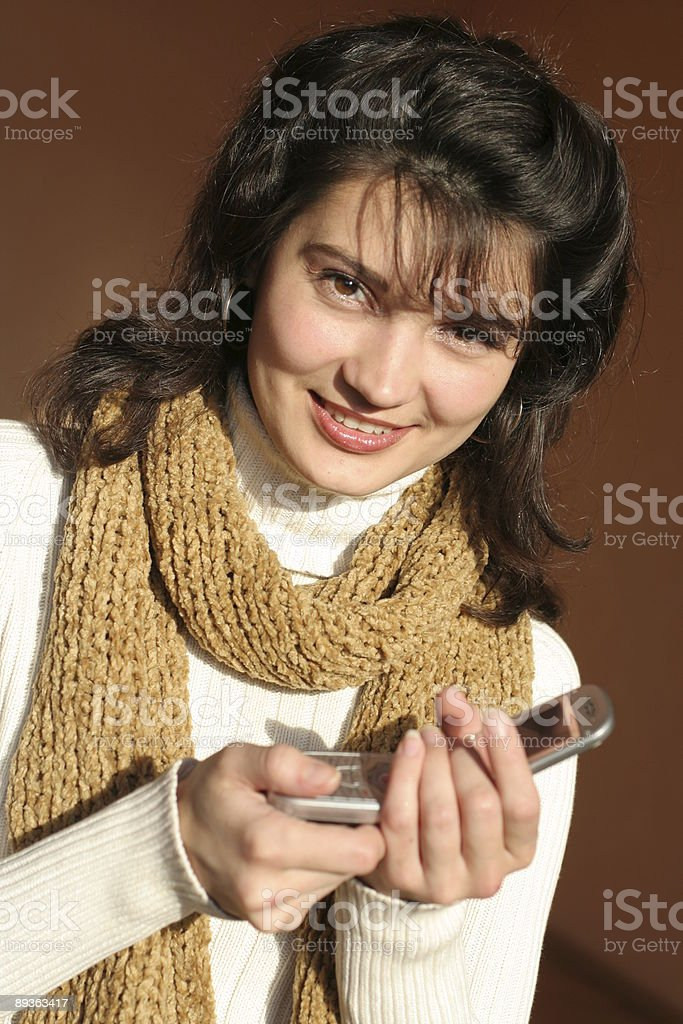 The girl in a scarf with mobile telephone. royalty-free stock photo