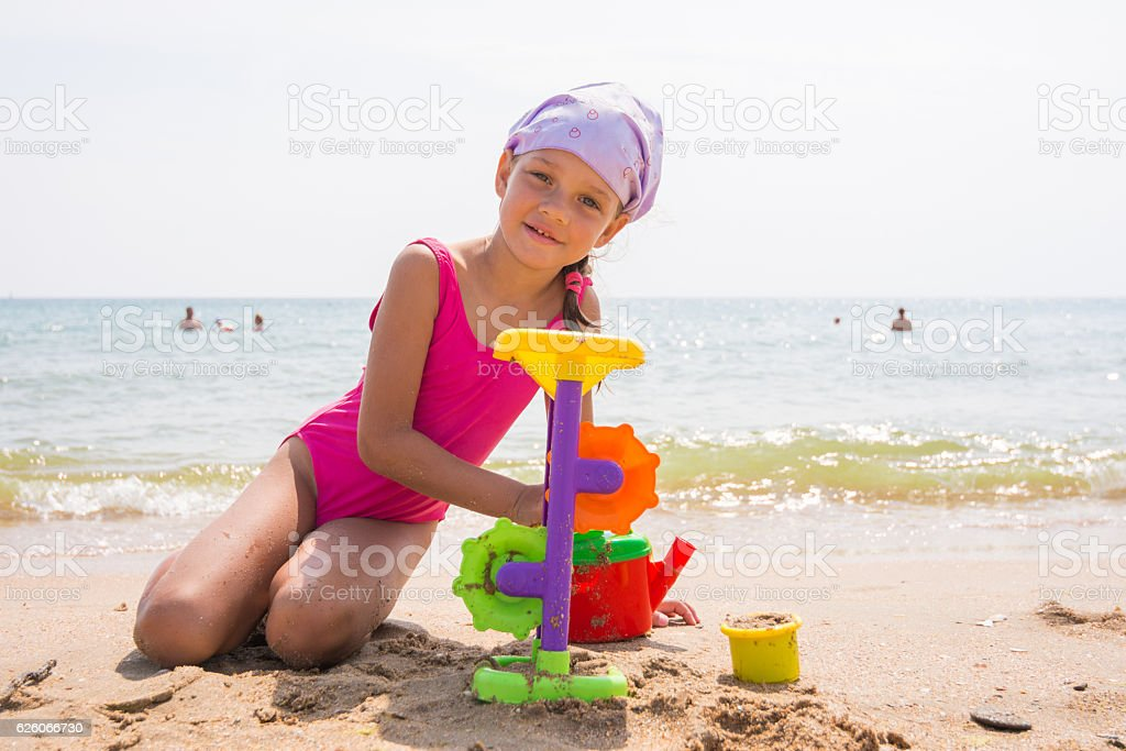 The girl in pink swimsuit playing with sand toys stock photo