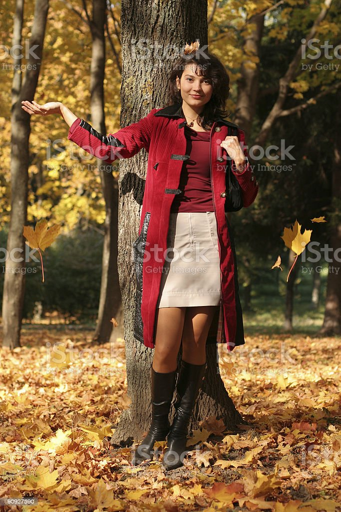 The girl in red and falling foliage. royalty-free stock photo