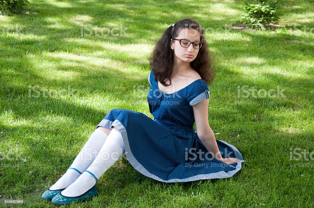The girl in the blue dress sitting with eyes closed stock photo
