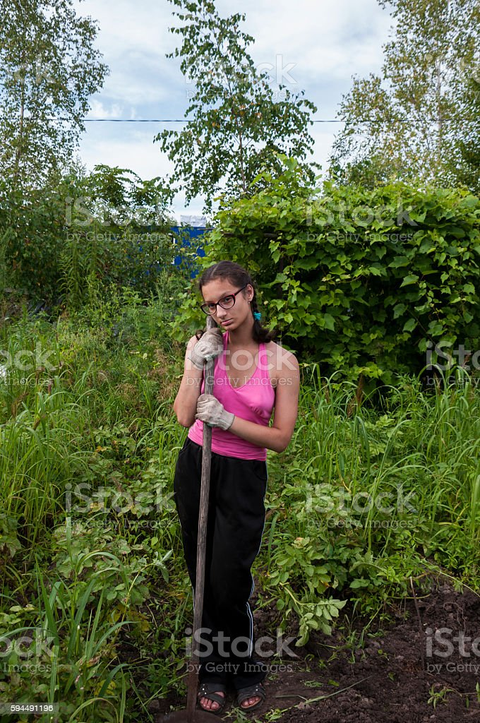 The girl in the garden with a hoe is stock photo