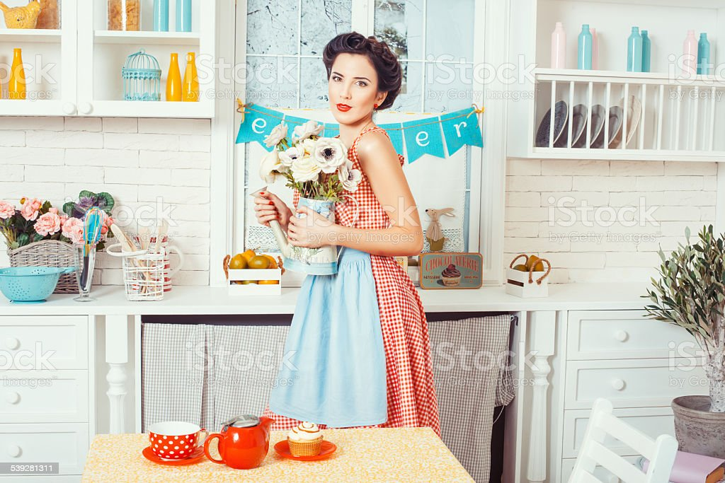 The girl in the kitchen with flowers. stock photo
