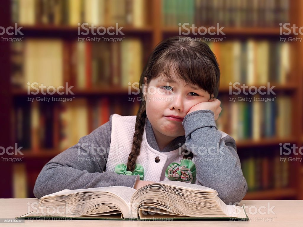 The girl in the library with a book and glasses stock photo
