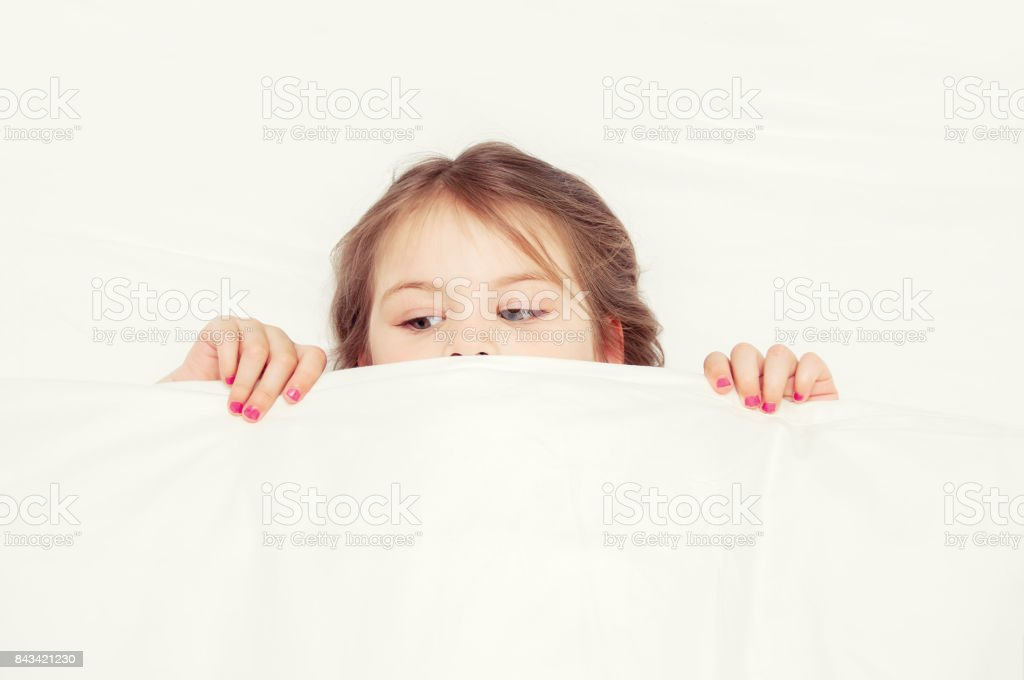 The girl is lying on the couch in the bedroom and covered herself with a blanket for fear. Little girl having childhood nightmares and fears hiding under the blanket. stock photo