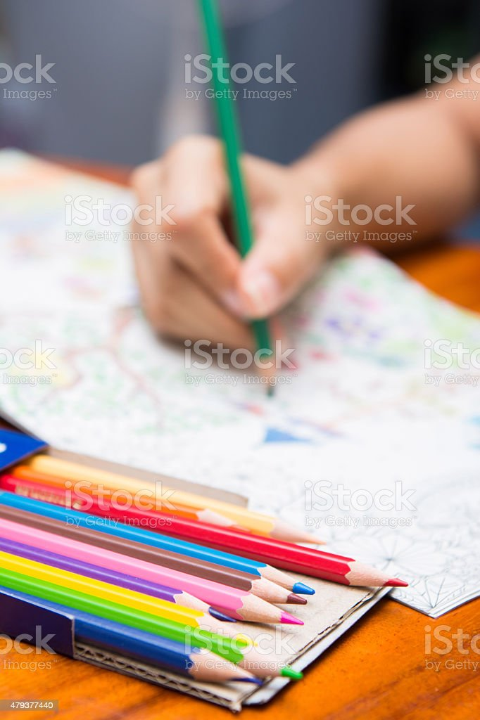 the girl is painting on coloring books stock photo