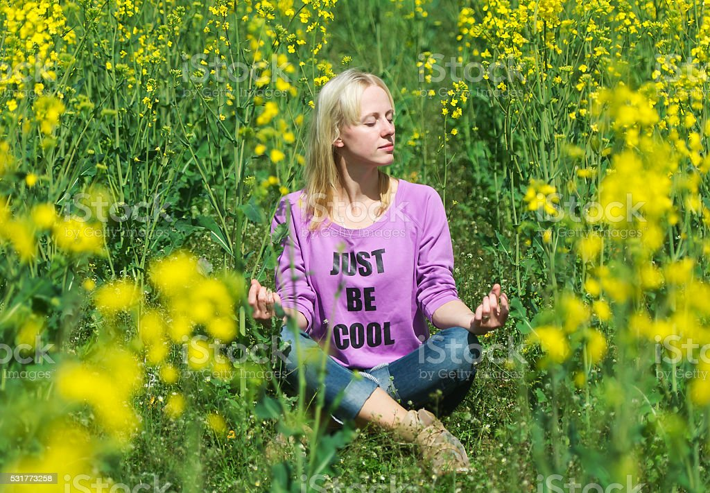 The girl meditates in a grass. stock photo