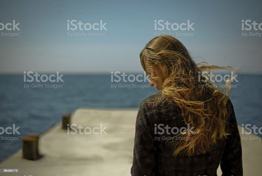The girl on seacoast during a storm stock photo