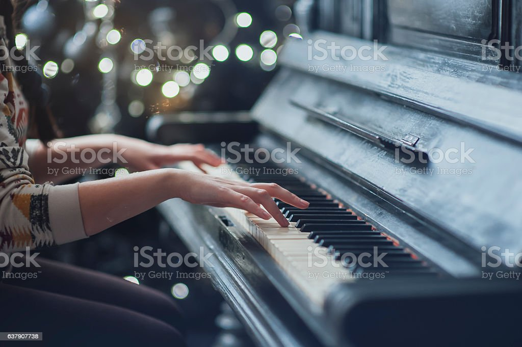 The girl plays piano, close up , white and black keyboard stock photo