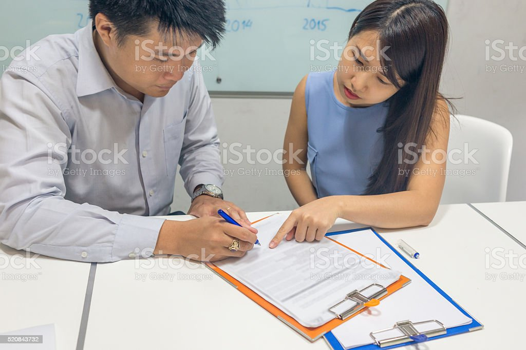 The girl showing the man blank space to sign document stock photo