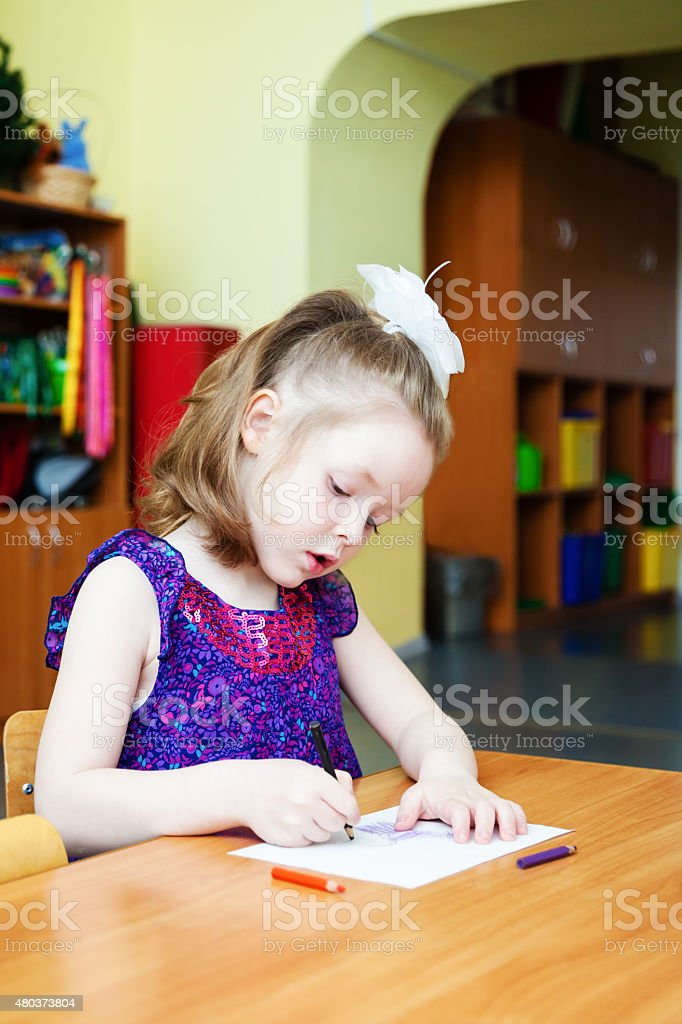 The girl sitting at the table and drawing stock photo