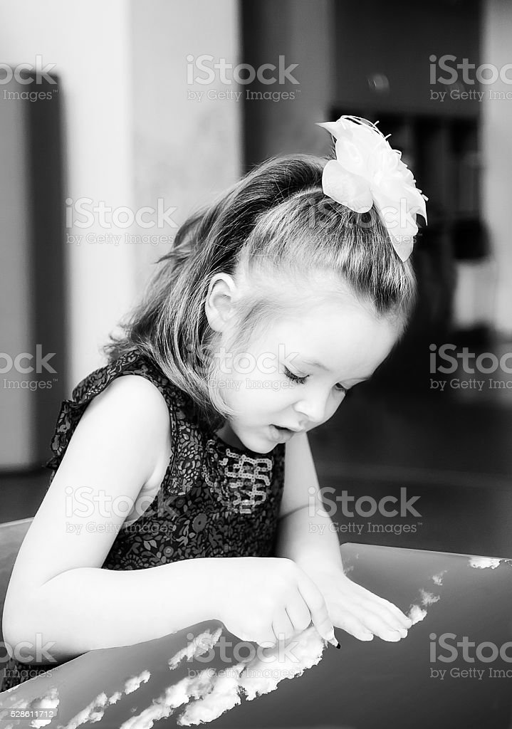 The girl sitting at the table and drawing with pencils stock photo