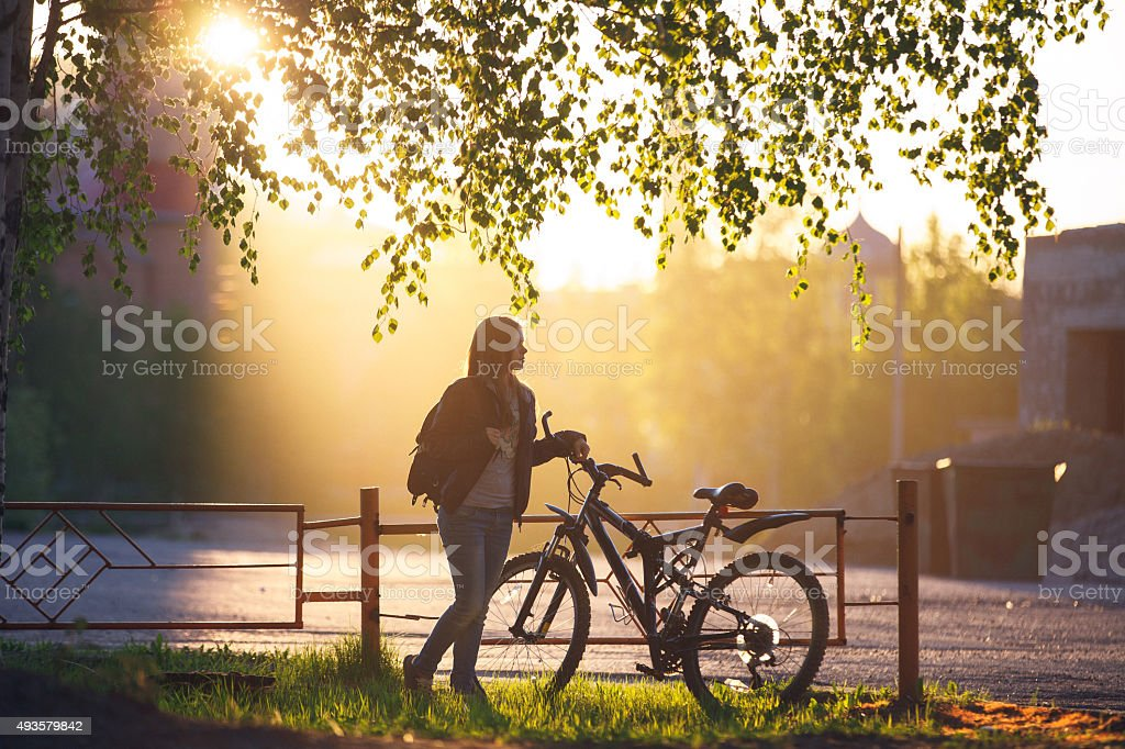 The girl standing next to bicycle stock photo