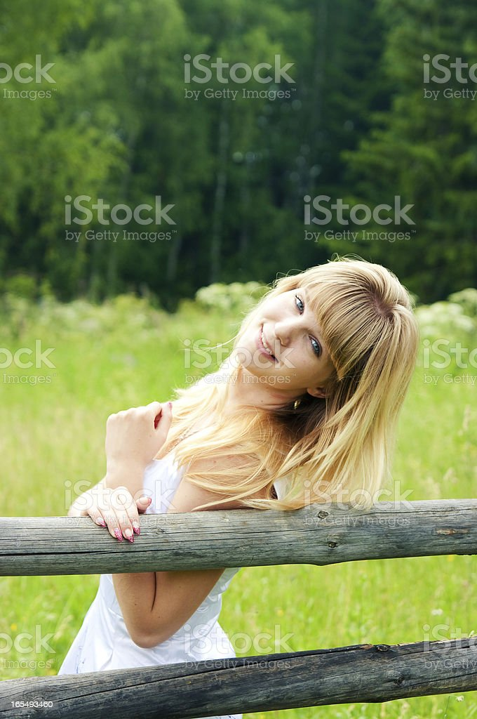 the girl stands near a fence royalty-free stock photo