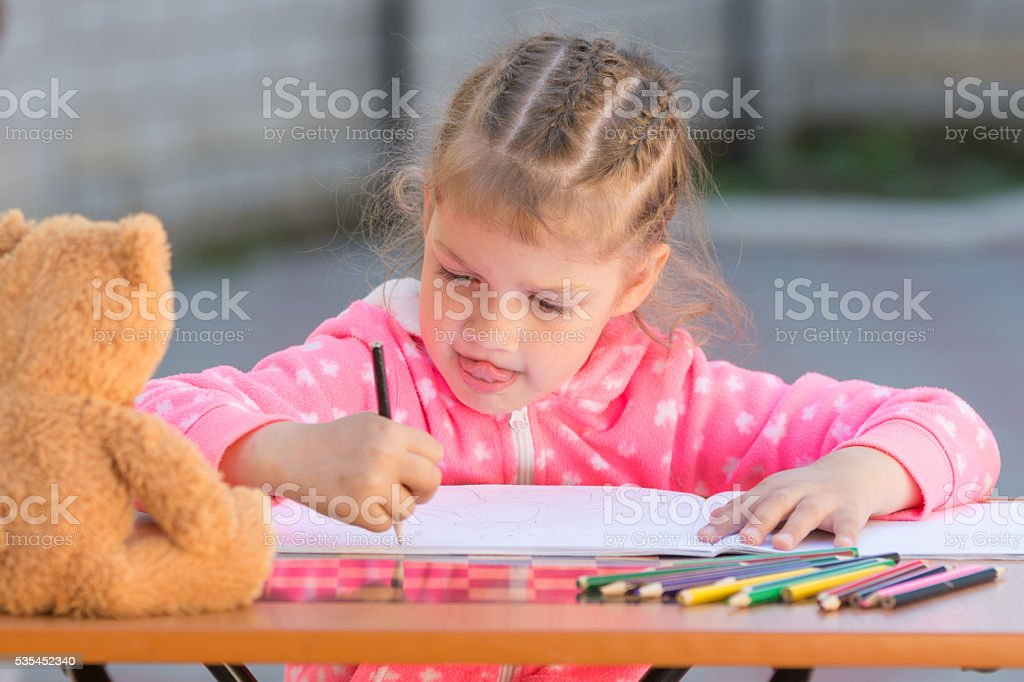 The girl stuck out her tongue enthusiastically drawing stock photo