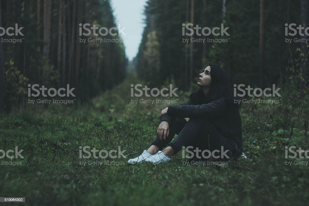 The girl thoughtfully sitting in the woods stock photo