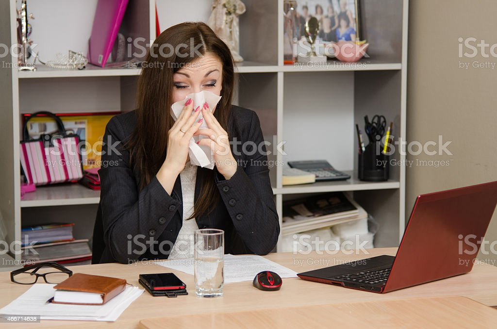 The girl wiping nose with a tissue in the office stock photo