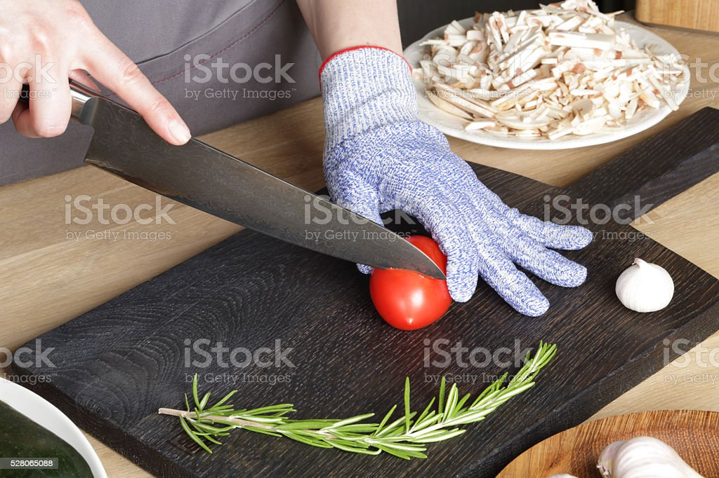 The girl with a knife cuts  tomato stock photo
