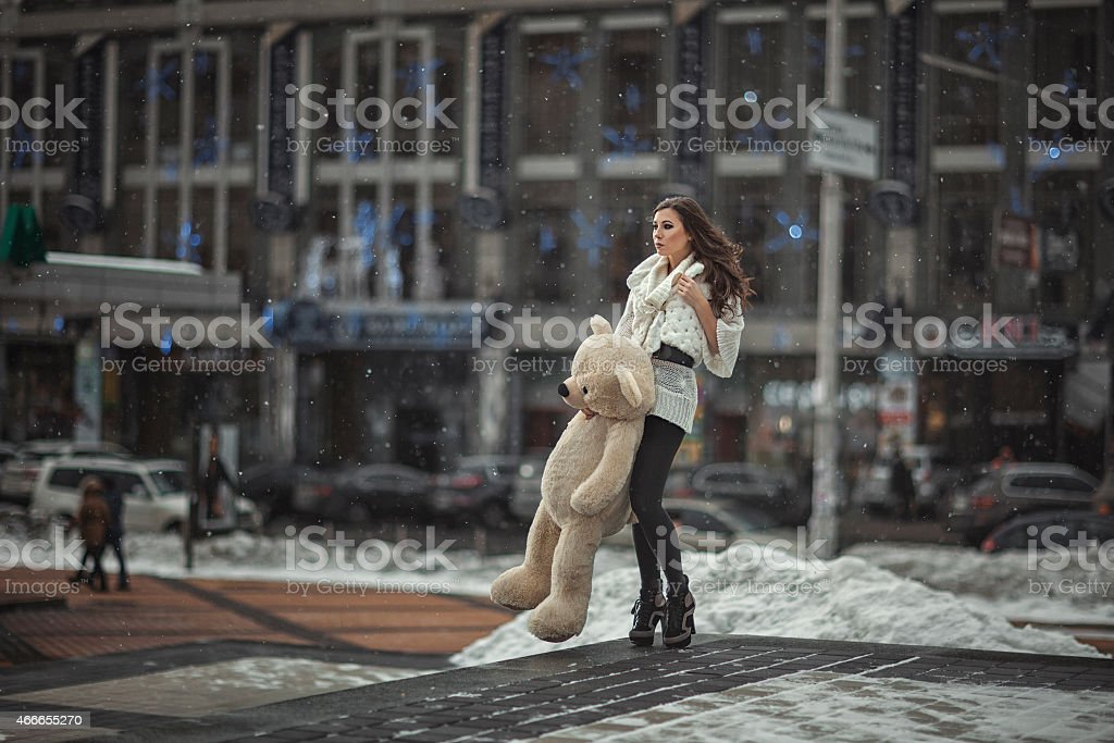 The girl with a toy bear in the city. stock photo