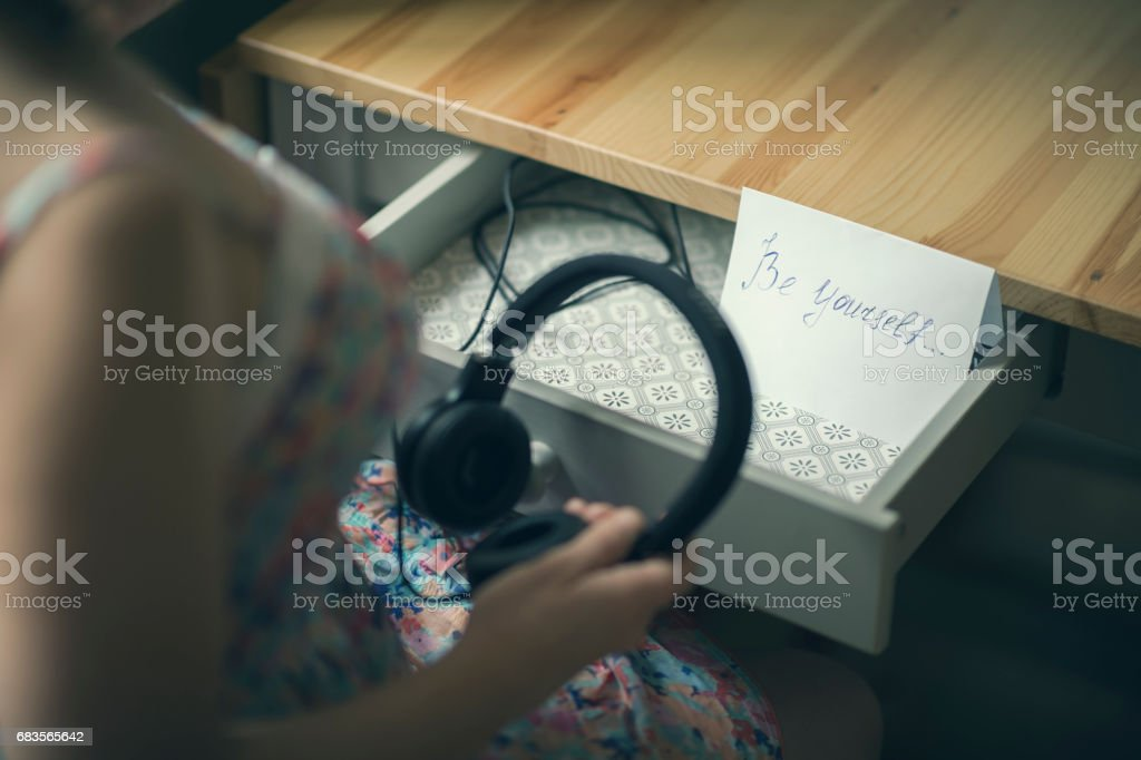 The girl with headphones and  message be yourself. The inscription on the paper be yourself. The concept of friendship and relationships. stock photo