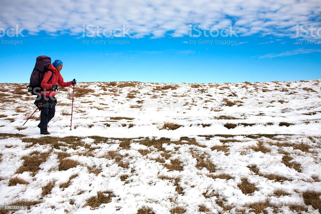The girl with the backpack goes on a mountain trail. stock photo
