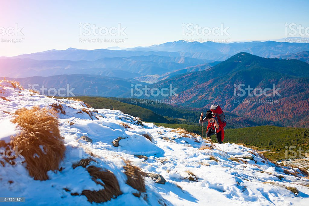 The girl with the backpack goes through the snow. stock photo